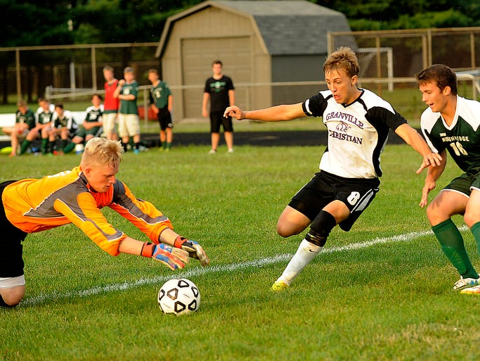 Northridge goalkeeper Skyler Pritts dives on the ball before Granville Christian forward Caleb Patton can score as defender Tate Van Fossen backs him up. The Lions defeated the Vikings 5-4 on Friday, Aug. 22, 2014.
