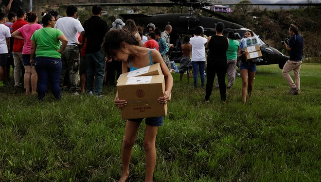 "A young girl looks back after getting her shoe stuck in the mud while carrying supplies delivered by soldiers working with a 101st Airborne Division ""Dustoff"" unit during recovery efforts following Hurricane Maria."