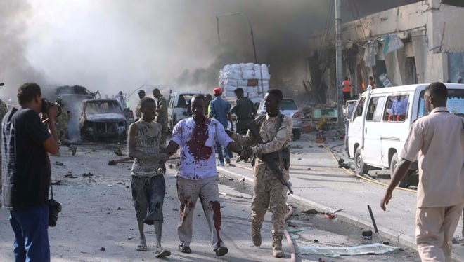A Somali government soldier evacuates an injured man from the scene of an explosion in Mogadishu, in October this year.