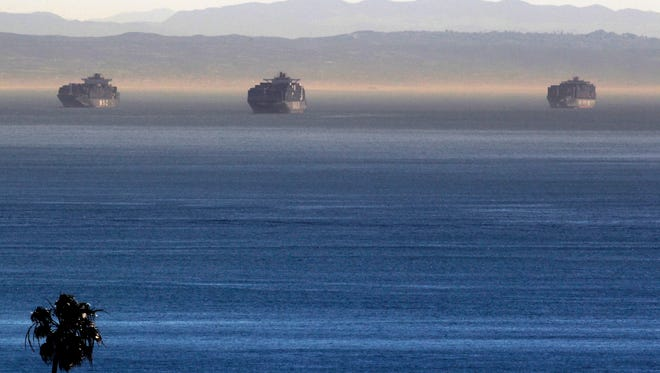 Cargo ships stand at anchor outside the Ports of Los Angeles and Long Beach, seen in this view from the San Pedro area of Los Angeles, Thursday. Seaports in major West Coast cities that normally are abuzz with the sound of commerce are falling quiet as a result of a labor dispute between employers and dock workers.