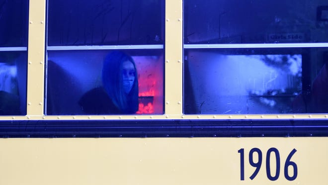 A student wears a mask as she rides a school bus near Evans High School during the first day of classes in Evans, Ga., Monday morning, August 3, 2020.