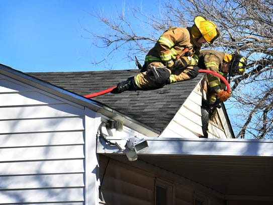 Wichita Falls firefighters work from the roof of a