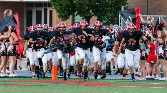 Pewaukee senior Blaze Beltran (76) leads the team onto the field prior to the game at home against Wisconsin Lutheran on Friday, August 26, 2016.