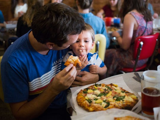 Kevin Neitzer feeds his son, Kase Neitzer, 2, pizza during the free pizza special for kids at SummaJoe's on Wednesday, September 7, 2016 in Anderson.