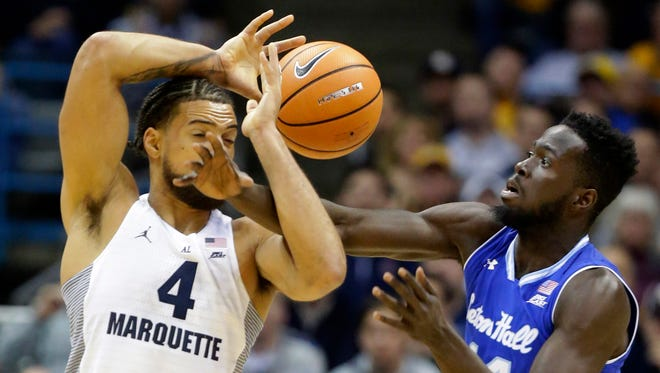Marquette freshman Theo John and Seton Hall forward Ismael Sanogo battle for a loose ball on Tuesday.