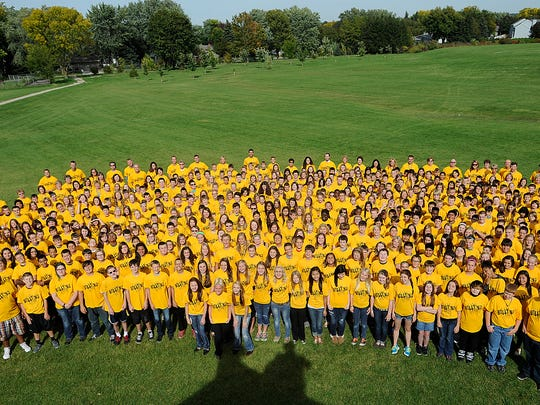 "Theisen Middle School took a stand against bullying in September 2013. Students gathered for an all school photo wearing ""Not in Our House"" T-shirts."