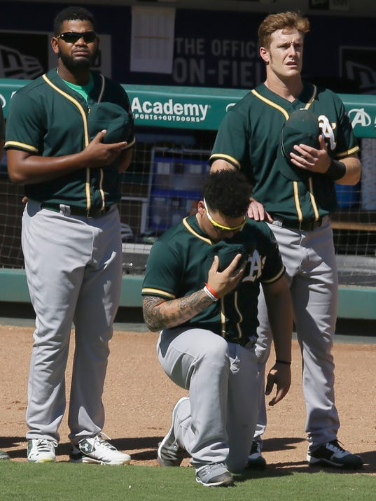 FILE - In this Sunday, Oct. 1, 2017 file photo, Oakland Athletics catcher Bruce Maxwell takes a knee during the national anthem next to teammates Mark Canha, right, and Raul Alcantara before a baseball game against the Texas Rangers in Arlington, Texas. Oakland Athletics catcher Bruce Maxwell says he will no longer kneel for the national anthem as he did last season as a rookie, when he became the first major leaguer to do so following the lead of many NFL players. He spoke Tuesday, Feb. 13, 2018 as the A's pitchers and catchers reported to spring training. (AP Photo/LM Otero, File)