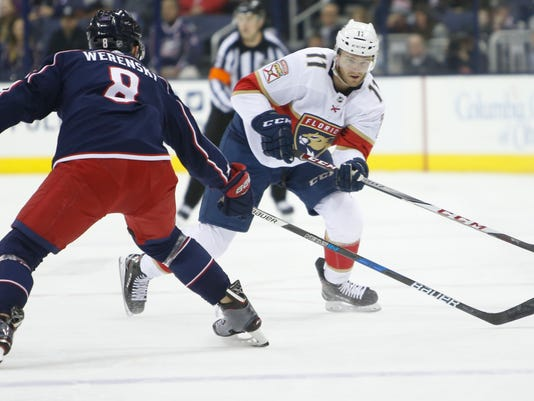 Florida Panthers' Jonathan Huberdeau, right, dumps the puck across the blue line past Columbus Blue Jackets' Zach Werenski during the first period of an NHL hockey game Sunday, Jan. 7, 2018, in Columbus, Ohio. (AP Photo/Jay LaPrete)