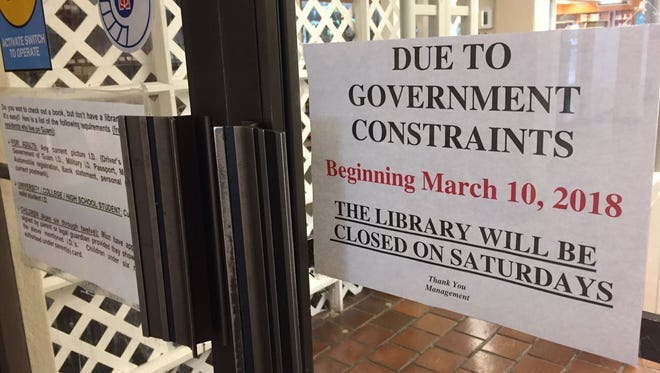 A sign at the Nieves M. Flores Memorial Library in Hagåtña on March 7, 2018 shows that it will be closed on Saturdays due to government constraints.