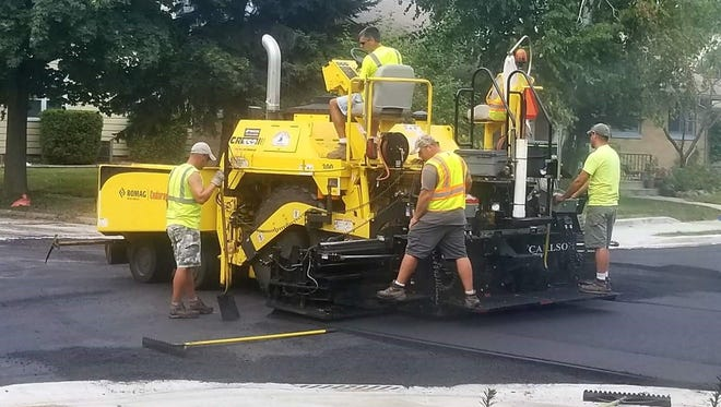 From left: Tim Allee, Nick Binsfeld (seated), Bob McNitt and Mark Wilhelm operate the City of Sheboygan's asphalt paving machine.