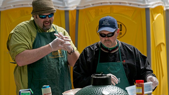 Schyler Sheffield, left, looks on as Buck Hall, right, with Pensacola Egg Fest, prepares for the team's meats for lat year's Smokin' in the Square. The two-day barbecue festival returns Friday.