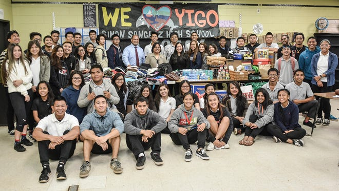 "Students from Simon Sanchez's English 12 Legacy class gather around their collected donations of food, clothing, and household supplies for victims of Typhoon Dolphin on May 28. Standing with the students are Superintendent Jon Fernandez, who rewarded the group with a $100 check, and Yigo Mayor Rudy Matanane, who received the donations on behalf of his village. Luke Fernandez, Legacy president and Sanchez senior, thanked his teacher Mrs. Acie Jo cruz for inspiring the group to take action. ""We knew we had to do something because this is our school, and this is our community,"" said Fernandez."