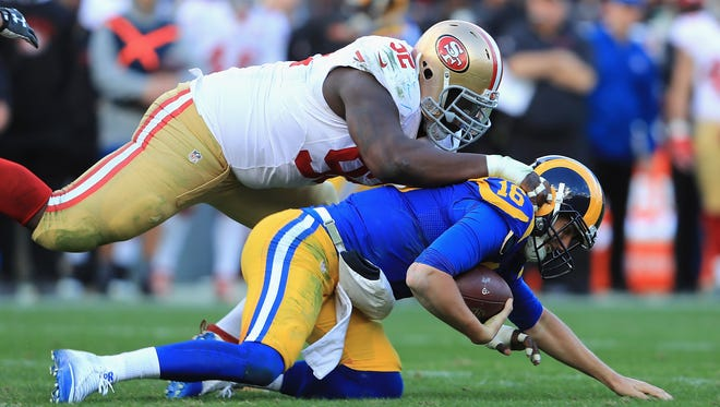 San Francisco 49ers defensive tackle Quinton Dial tackles Los Angeles Rams quarterback Jared Goff during the first half of their game at Los Angeles Memorial Coliseum on December 24, 2016 in Los Angeles.