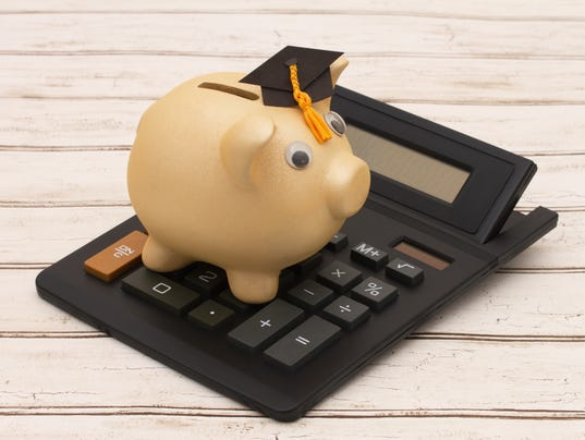 Golden piggy bank with grad cap and calculator on wood
