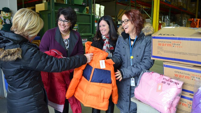 State Rep. Laura Cox (from left), Livonia Public Schools Superintendent Andrea Oquist and teachers Colleen Nowak and Catherine Trapp check out the winter coats that were donated to the school district for students in need this winter season.