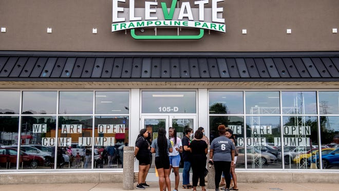 A small crowd gathers Tuesday, June 30, 2020 outside Elevate Trampoline Park to talk with the managers of the facility and protest a racially-charged incident that happened there Saturday night.