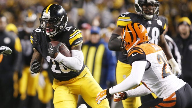 Pittsburgh Steelers running back Le'Veon Bell (26) runs after a catch as Cincinnati Bengals cornerback Leon Hall (29) defends during the second quarter at Heinz Field.