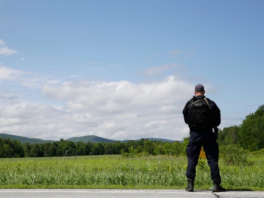 A heavily armed law enforcement officer patrols the edge of road during a search for two escaped killers in Boquet, N.Y., Tuesday, June 9, 2015.