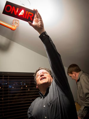 Randy Fox shows coworkers the front panel of the new on air light after unboxing it at the WXNA studio on Thursday.