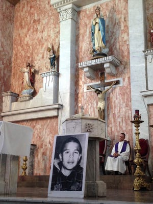 In this Oct. 14, 2014, photo, a photo of Jose Antonio Elena Rodriguez, who was fatally shot by U.S. Border Patrol near the Mexico-U.S border, leans against a podium on a church altar during a memorial mass in Nogales, Sonora, Mexico. The civil rights case against Agent Lonnie Swartz over the Rodriguez' death will go forward after U.S. District Court Judge Raner C. Collins denied a part of his motion to dismiss the case.