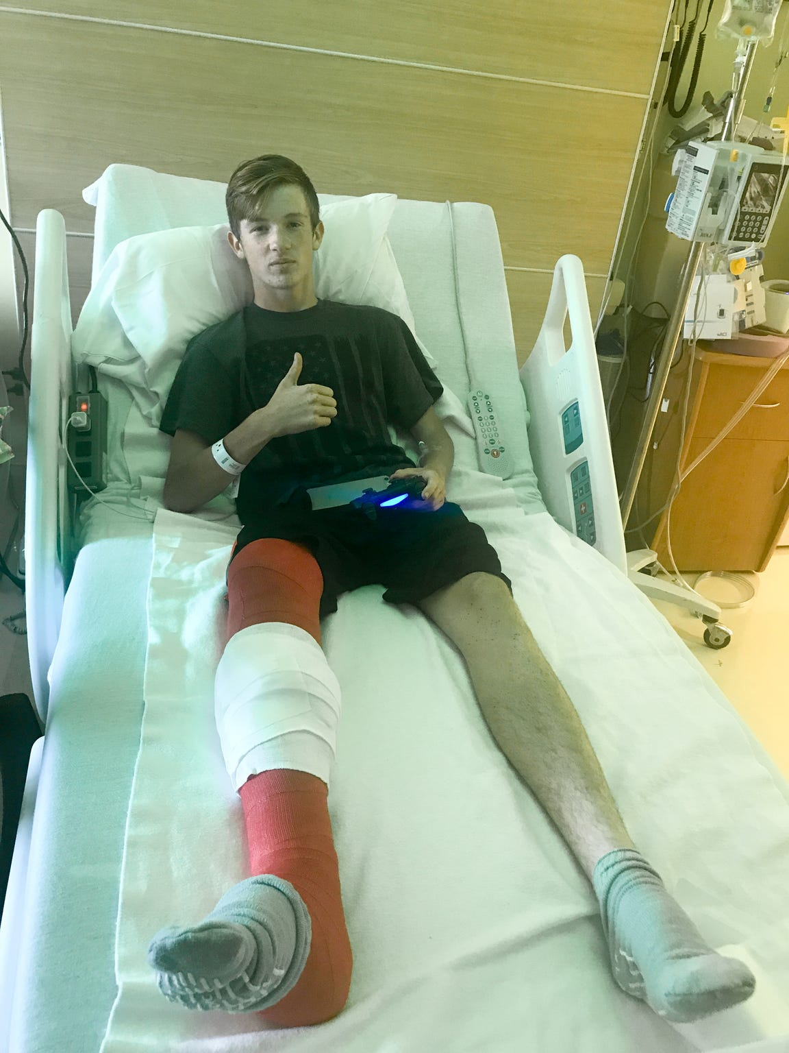 Walker Kinnison gives a thumbs up while resting in his hospital bed, shortly after a four-wheeler accident that broke his tibia and bones in his foot and ankle.