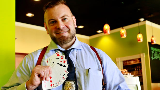 Detective George Ripley, of the York City Police Department, shows his cards at The Green Bean Roasting Co. in York City, Friday, June 9, 2017. Ripley often shares his magic with customers at the coffee shop as well as with those he might interview as a homicide detective. Dawn J. Sagert photo