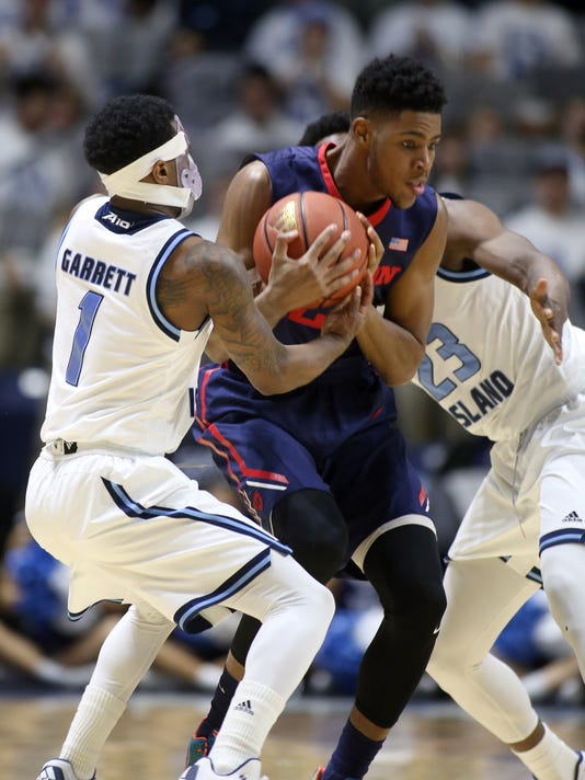 Rhode Island's Jarvis Garrett, left, steals the ball from Dayton's Xeyrius Williams as Rhode Island's Kuran Iverson closes in at right during the first half of an NCAA college basketball game in Kingston, R.I., on Friday, Feb. 12,2016. (AP Photo/Joe Giblin)