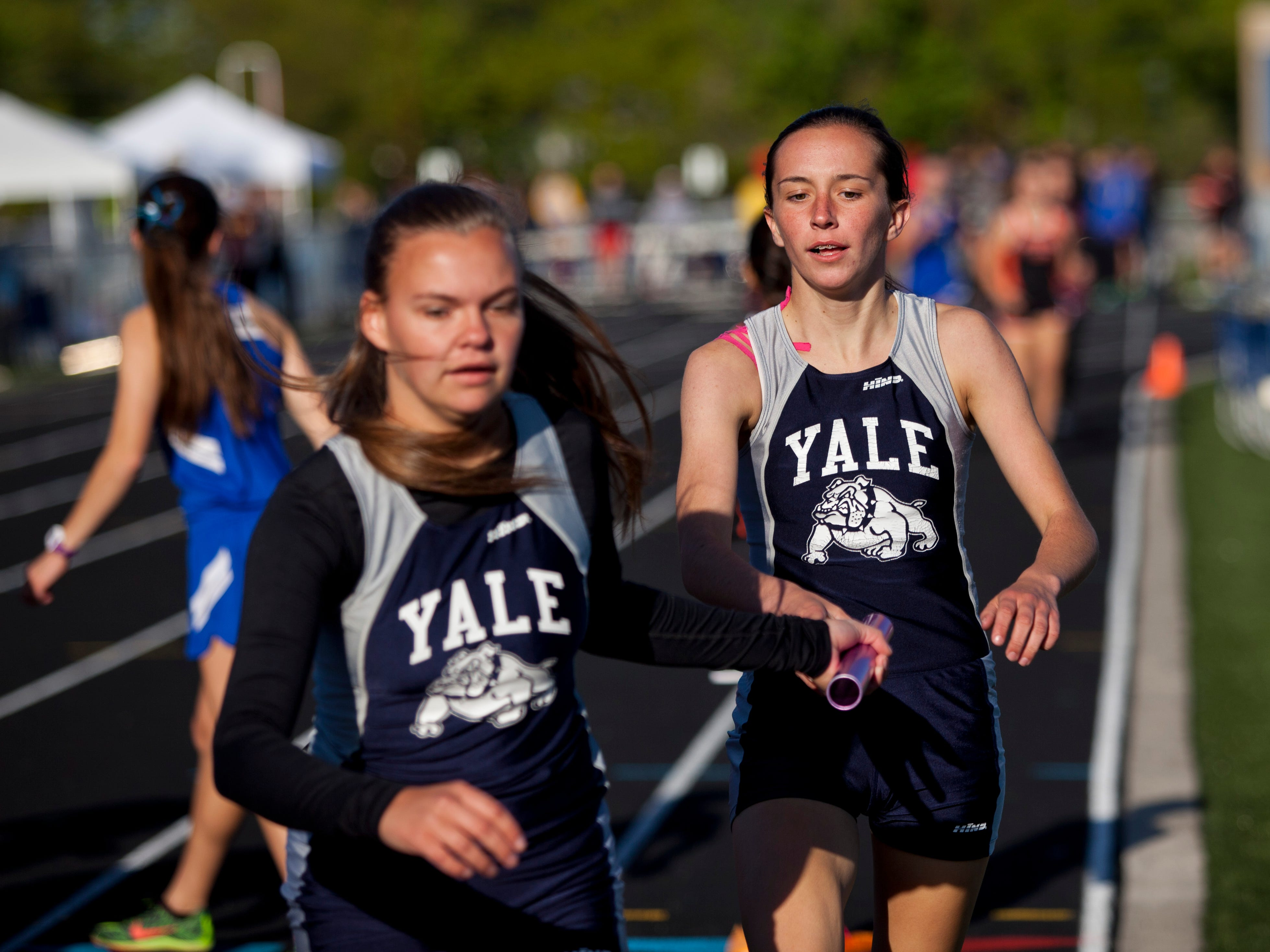 Yale junior Megan Dunsmore hands off the baton to sophomore Sophie Kincaid as they compete in the 2-mile relay during the Meet of Champions Friday, May 22, 2015 at Marysville High School.