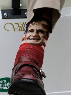 Former president George H.W. Bush wears socks bearing his image at the Houston Texans-New England Patriots game.