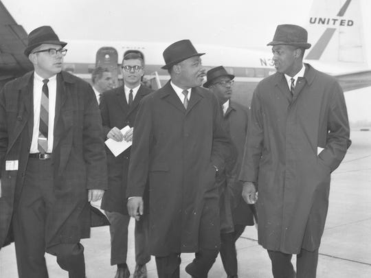 Dr. Robert L. Green, far right, walks with Dr. Martin Luther King Jr., center, as King arrives at the airport in Lansing on Feb. 11, 1965. King spoke to students at Michigan State University.