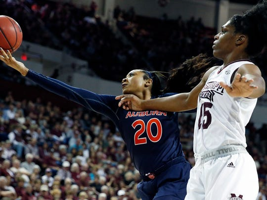 Auburn forward Unique Thompson (20) reaches for a rebound in front of Mississippi State center Teaira McCowan (15) during the second half of an NCAA college basketball game in Starkville, Miss., Thursday, Feb. 22, 2018. Mississippi State remained undefeated, winning 82-61. (AP Photo/Rogelio V. Solis)