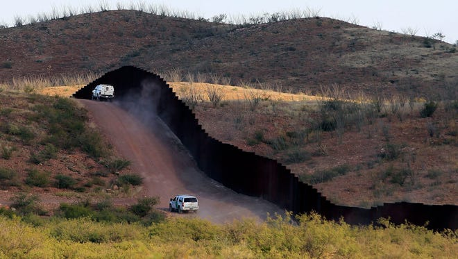 In this Oct. 2, 2012 file photo, U.S. Border Patrol agents patrol the border fence in Naco, Ariz.