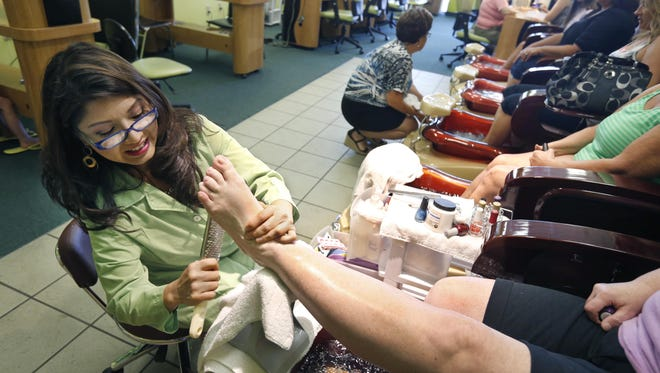 "Pro Nails owner Holly Phan Sackett give a pedicure to a customer in the Penfield salon. ""My customers, they are like my family,"" Sackett said."