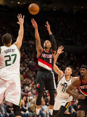 Portland Trail Blazers guard Damian Lillard shoots a basket as he is guarded by Utah Jazz center Rudy Gobert during the first half at Moda Center.