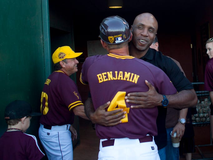 Former Giant's star and ASU grad Barry Bonds hugs ASU's  assistant coach Mike Benjamin before throwing out the first pitch before a game against Washington at Packard Stadium on Saturday, March 15, 2014 in Tempe, Az.