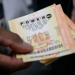 A customer holds Powerball tickets that he purchased Jan. 12, 2016, at Kavanagh Liquors in San Lorenzo, Calif.