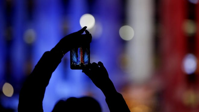A person photographs the building at 30 Rockefeller Plaza, illuminated in patriotic lights during an Election Night gathering at Rockefeller Center, Tuesday, Nov. 8, 2016, in New York. (AP Photo/Julio Cortez)