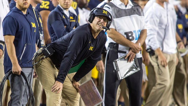 Michigan coach Jim Harbaugh looks at the scoreboard from the sideline in the first quarter during a game against Michigan State in Ann Arbor, Oct. 7, 2017.