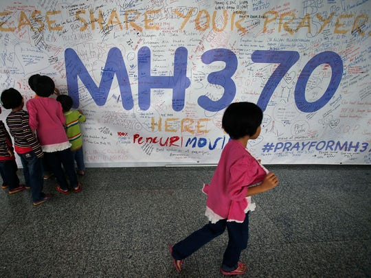 Children read messages and well wishes displayed for all involved with the missing Malaysia Airlines jetliner MH370 on the walls of the Kuala Lumpur International Airport in Sepang, Malaysia. As time passes since Malaysia Airlines Flight 370 disappeared with 239 people aboard, an exhaustive international search has produced no sign of the Boeing 777, raising an unsettling question: What if the airplane is never found?