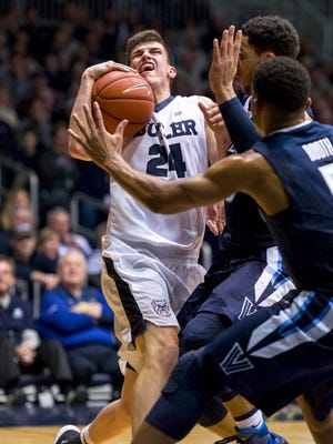 Butler guard Kellen Dunham (24) grimaces as the ball makes contact with his face en route to the basket against Villanova during the first half of an NCAA college basketball game, Sunday, Jan. 10, 2016, at Hinkle Fieldhouse.