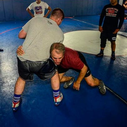 Rick Gumble  demonstrates a move on Zach Gifford, of Deposit, during a practice at Chenango Forks High School in 2014.
