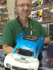 Hobby Town USA owner Tony Waterman with a remote controlled car.