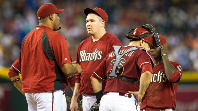 Arizona Diamondbacks pitching coach Mike Harkey (left) talks on the mound with starting pitcher Trevor Cahill in the fourth inning against the Detroit Tigers on Wednesday, July 23, 2014. in an interleague game at Chase Field on Wednesday, July 23, 2014.