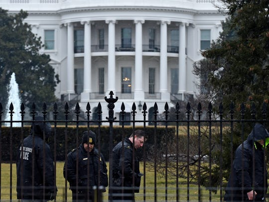 Secret Service officers search the south grounds of the White House in Washington, Jan. 26, 2015. The Secret Service says a small drone crashed overnight at the White House complex while the president was in India.