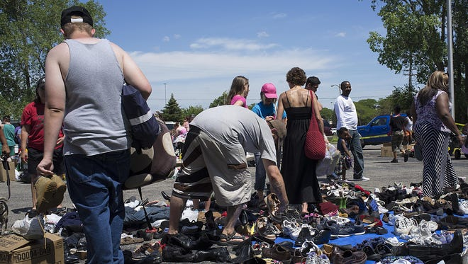 People look through a pile of shoes at the Homeless Angels Street Store event Sunday.