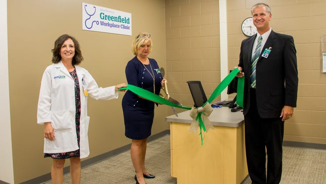 Physician Assistant Angela Montoto and Director of Human Resources Mark Kapocius hold the ceremonial ribbon for Superintendent Lisa Elliott to cut and officially open the district's new workplace clinic.