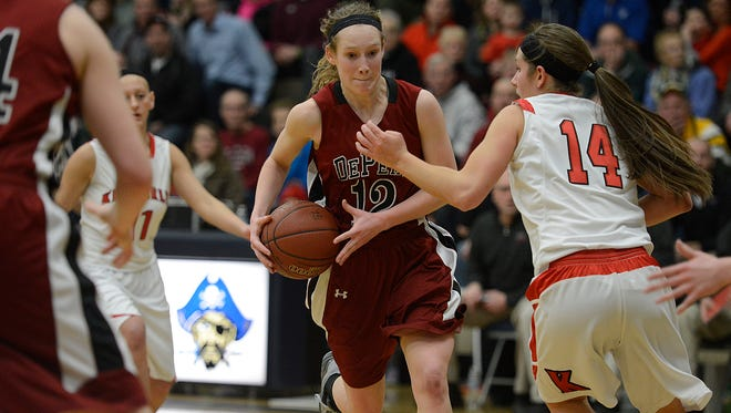 De Pere's Margaret Miller (12) drives to the basket against Kimberly's Jenna Smarzinski (14) during Thursday night's WIAA Division 1 Sectional semifinal game at Bay Port High School in Suamico. Evan Siegle/Press-Gazette Media