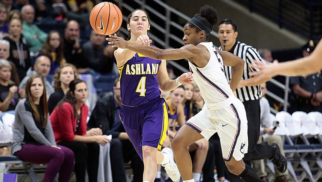 Former Crestview star Renee Stimpert  of Ashland University passes through the arms of University of Connecticut's Crystal Dangerfield during Sunday's preseason game at Gampel Pavilion in Storrs, Connecticut.