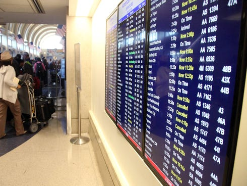A departure board shows flights canceled due to severe weather on the East Coast on  Friday at Los Angeles International Airport. Delays and cancellations persisted across the country on Monday.