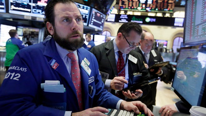 Specialist Michael Pistillo, left, works with traders at his post on the floor of the New York Stock Exchange on Wednesday.